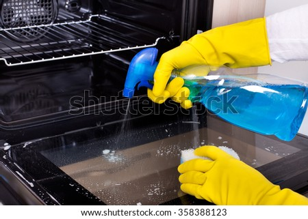 Close up of female hand with yellow protective gloves spraying detergent from bottle on the oven door