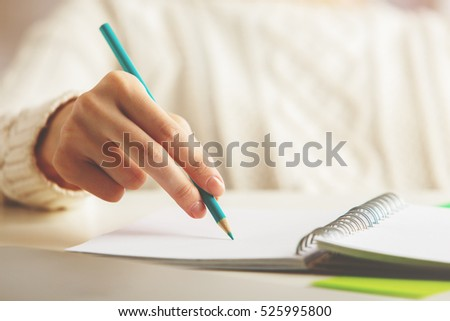 Close up of female hand writing in spiral notepad on desktop