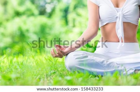 Close up of female hand zen gesturing. Girl sits in asana position. Concept of healthy lifestyle and relaxation