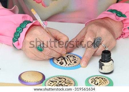 close-up of female hands artist in Tatar national costume, making Arabic calligraphy painting