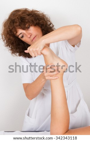 Close-up of female hands doing foot massage - reflexology