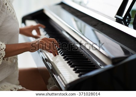 Close-up of female hands fingering piano keys