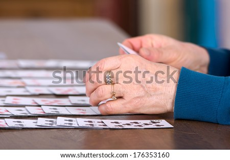 Close up of female hands holding cards and playing solitaire - stock photo