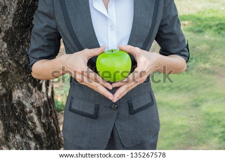 Close-up of female hands holding green apple outdoors