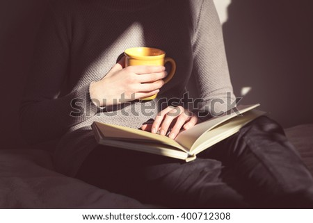 Close-up of female hands holding open book. Woman reading book.