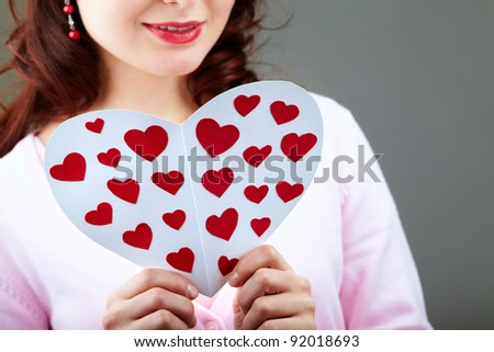 Close-up of female hands holding valentine card while reading it
