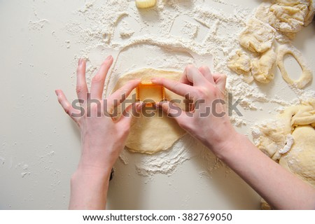 close up of female hands making cookies from fresh dough at home. dough, flour, baking tins on a white table in the background. - stock photo