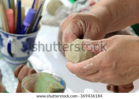 close-up of female hands master on clay; making small toys