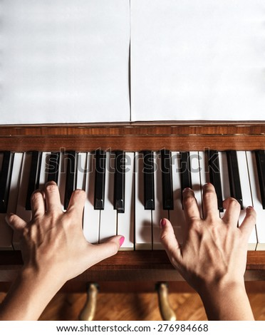 Close up of female hands playing piano - stock photo