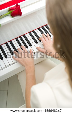Close up of female hands playing piano and red rose lying on it. Concept of music and art