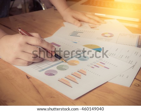 Close-up of female hands pointing at turnover graph while discussing it on wooden desk in office with morning light. Vintage filter effect. - stock photo