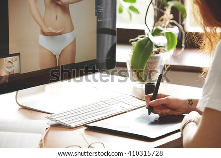 Close-up of female hands retouching photos using digital tablet. Cropped portrait of young woman freelancer using graphic tablet and computer while working at home. Selective focus. Home interior  - stock photo