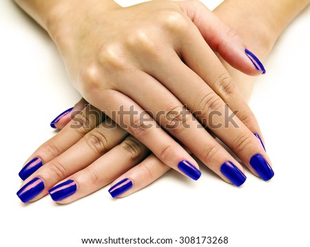 Close up of female hands showing colorful nail polish on white background.  The woman is wearing blue manicure. - stock photo