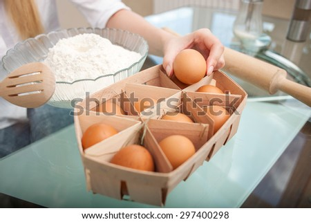 Close up of female hands taking an egg from basket on table. She is cooking tasty pastry with flour - stock photo
