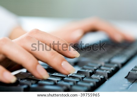 Close-up of female hands touching buttons of black keyboard - stock photo
