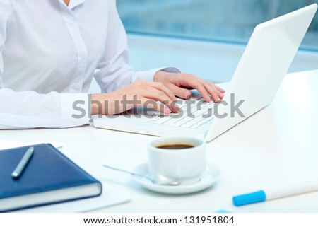 Close-up of female hands typing on laptop - stock photo