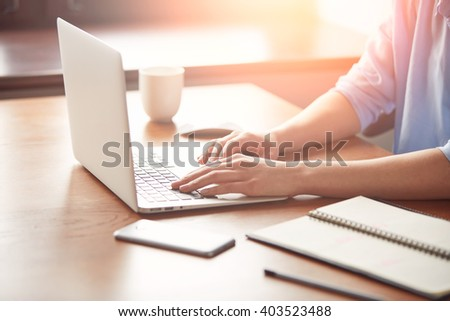 Close-up of female hands typing on the laptop, young student girl in blue shirt keyboarding on the notebook while enjoying her coffee in cozy café after lectures at university  - stock photo