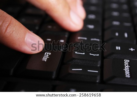 Close-up of female hands typing text on the keyboard of laptop or computer - stock photo