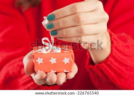 Close-up of female hands unpacking a present. - stock photo