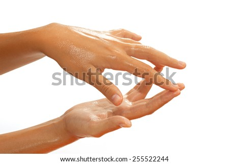 Close-up of female hands while applying oil on white background view 5 - stock photo