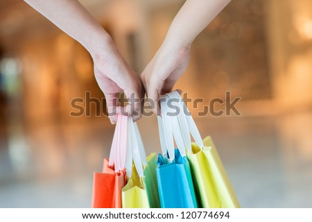 Close-up of female hands with paper bags - stock photo