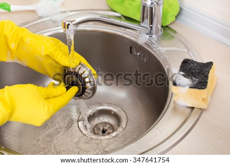 Close up of female hands with rubber gloves cleaning kitchen sink and drain
