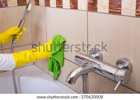 Close up of female hands with rubber gloves cleaning tiles in the bathroom