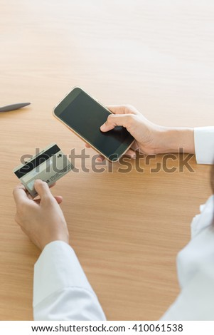 Close-up of female hands. Woman use smartphone writing something and holding credit card. purchase concept