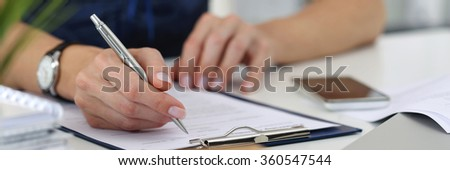 Close-up of female hands. Woman writting something and looking at mobile phone screen sitting at her office. Letter box format - stock photo