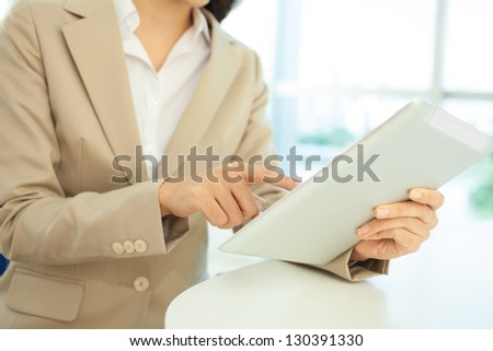 Close-up of female hands working with tablet-pc - stock photo