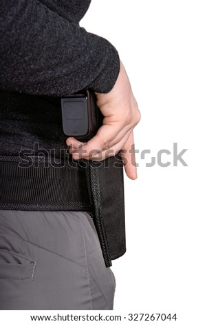 Close up of female holding hand on a gun in a holster on a white background