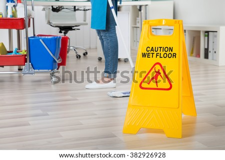 Close-up Of Female Janitor Mopping Wooden Floor With Caution Sign - stock photo