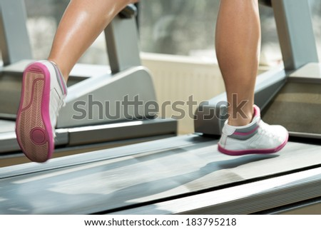 Close-Up Of Female Legs Running On Treadmill - Blurred Motion - stock photo