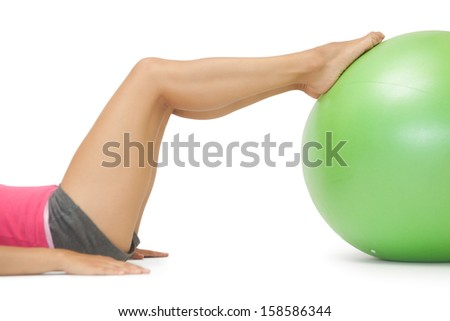 Close up of female legs with exercise ball on white background - stock photo