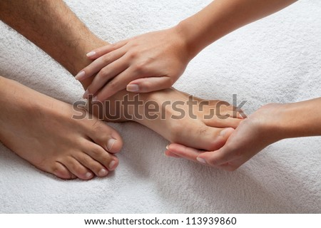 Close up of female masseuse giving a foot massage to man - stock photo