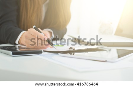 Close up of female office worker's hands doing accounting with calculator and laptop. - stock photo