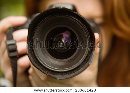 Close up of female photographer at the park - stock photo