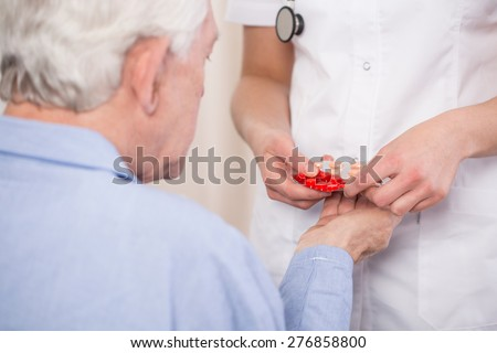 Close-up of female physician giving medicine to aged man - stock photo