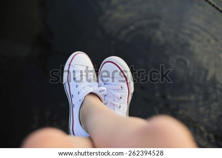Close up of  female's feet relaxing by the river - stock photo