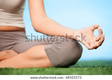 Close-up of female?s knee during meditation in pose of lotus with her legs crossed - stock photo