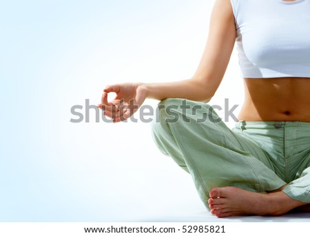 Close-up of female?s torso during meditation with legs crossed and hand being kept on her right knee - stock photo