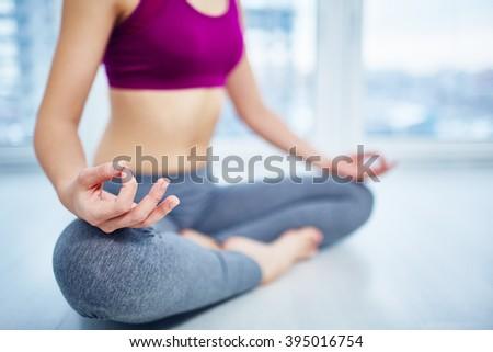 Close-up of female sitting cross legged during meditation - stock photo