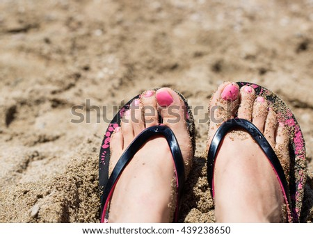 Close up of female sunbathing feet wearing flip flops near sea on sandy beach  - stock photo