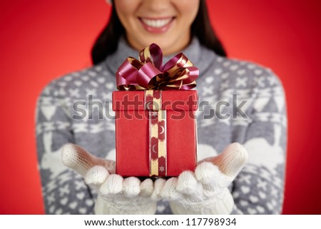 Close-up of female with giftbox on her gloved palms - stock photo