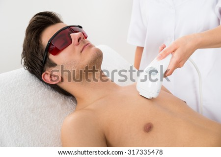 Close-up Of Female Worker Giving Man Laser Epilation On Chest In Salon - stock photo