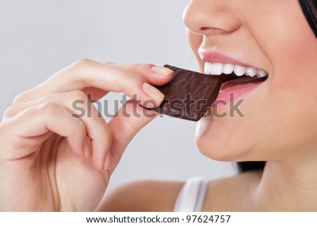close up of females mouth with slice of the chocolate
