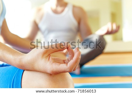 Close-up of feminine and masculine arms and crossed legs during meditation - stock photo