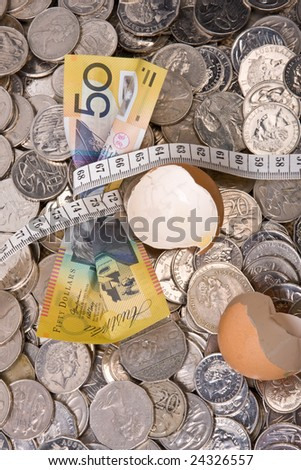 close up of fifty dollar note - with tape measure tightened and broken egg shell - stock photo