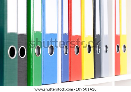 Close-up of file folders on the shelves at office - stock photo
