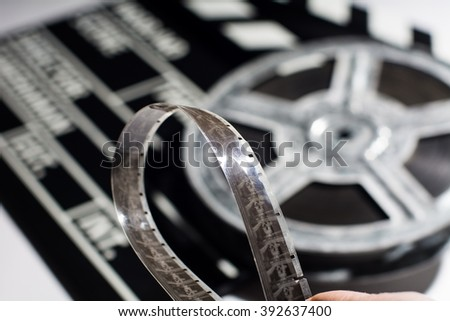 Close-up of film tape on background of film roll and clap cinema - stock photo